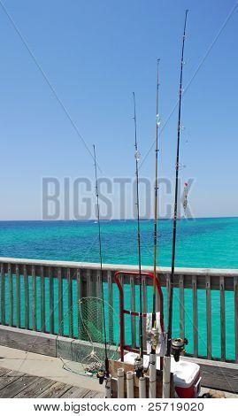Surtido de cañas de pescar y trastos en muelle con hermoso océano en la distancia