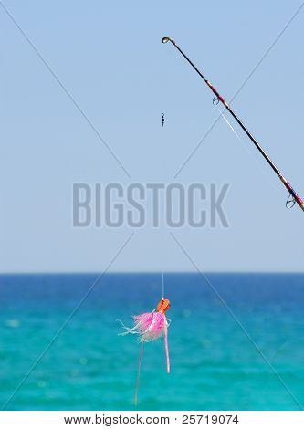 Bright pink fishing lure on pole with gorgeous ocean in distance