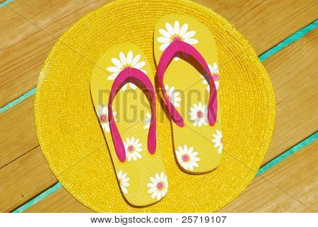 Yellow flipflops on dock over pretty ocean water