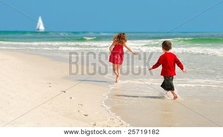 Kids running on pretty beach with sailboat  in distance