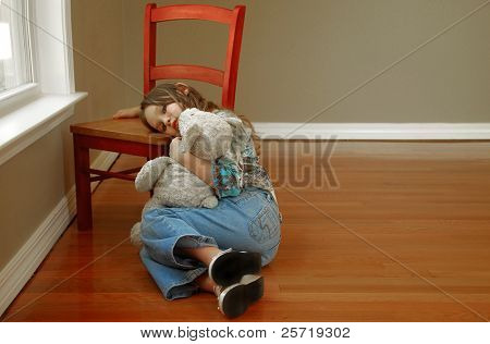 Young girl alone in room looking sad holding stuffed toy