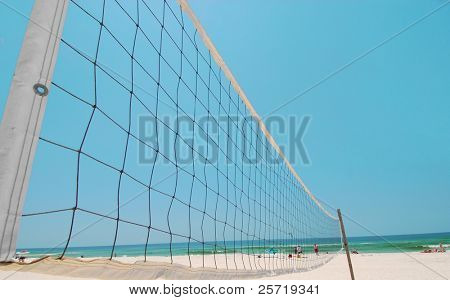 Volleyball net on pretty beach under blue sky