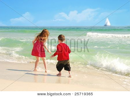 Young girl and boy playing happily in surf at pretty beach