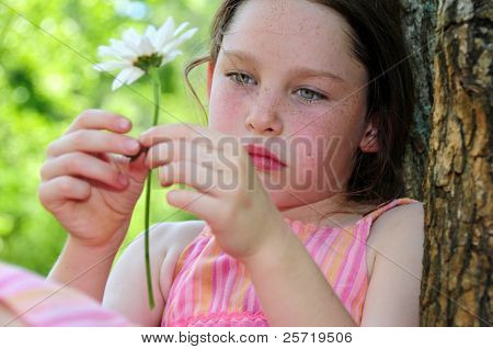 Young girl looking thoughtful or sad sitting by tree holding flower
