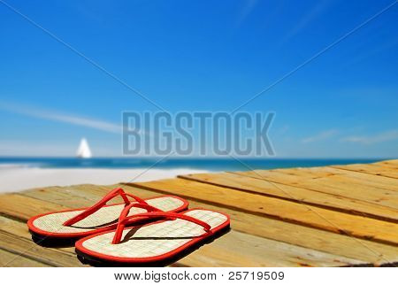 Flip flops on dock with sailboat in distance