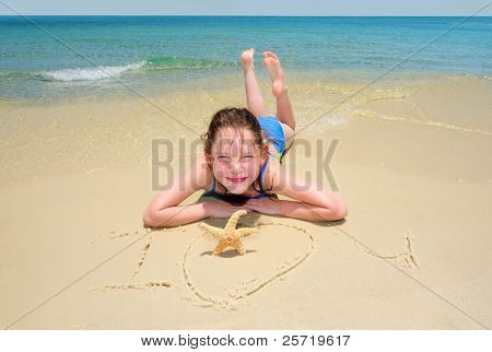 Young girl by I Love You message written in sand by starfish