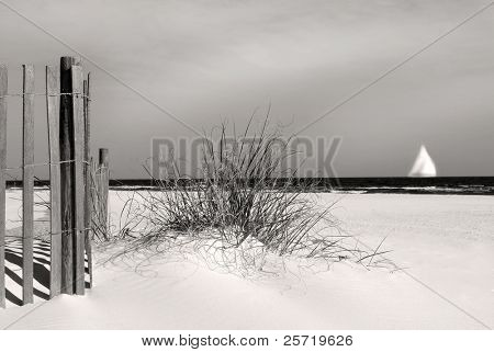 Sand dune and beach fence with sailboat on horizon