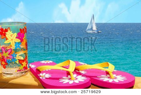 Flip flops and refreshing drink on rail overlooking sailboat on ocean