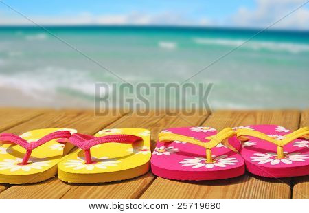 Colorful flipflop sandals on boardwalk by pretty shore