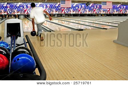Stacked bowling balls at festive lanes with bowler in distance