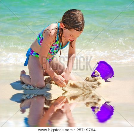 Young girl playing in sand on beach next to reflecting tide pool