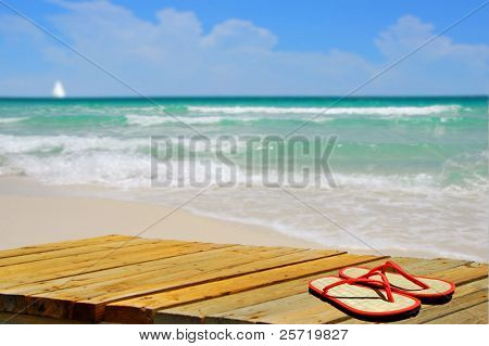 Beautiful deserted beach with colorful flipflops on pier