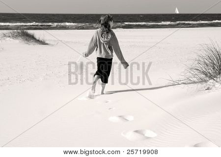 Young girl with pail exploring over dunes on pretty beach