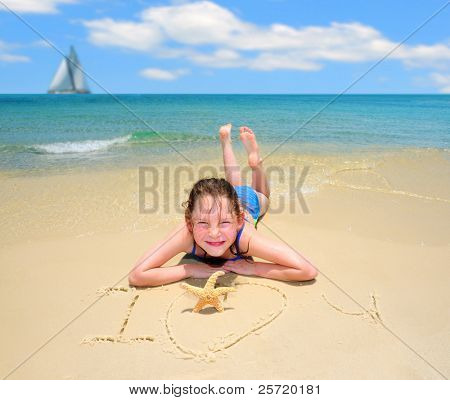 Girl and starfish by I Love You written in  sand