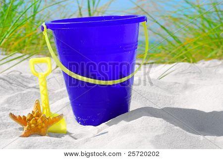 Sand pail and starfish on beach sand
