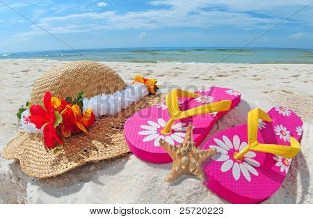 Colorful flipflops and hat by starfish on pretty beach
