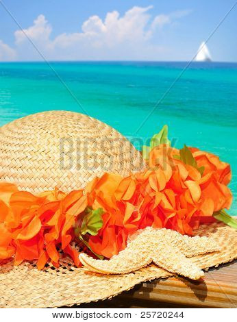 Straw hat and starfish overlooking gorgeous ocean with sailboat in distance