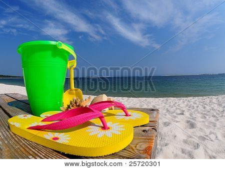 Colorful flipflops, beach pail, and shells on boardwalk by ocean