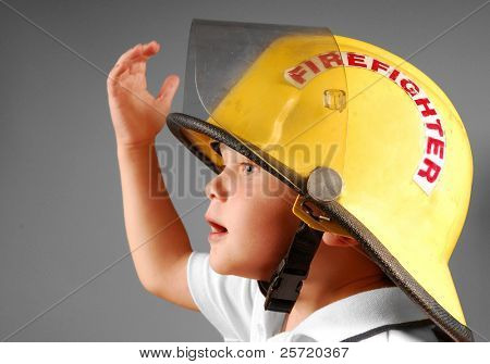 Cute young boy trying on real fireman's helmet