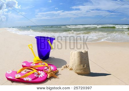 Pretty sand castle on seashore by beach accessories