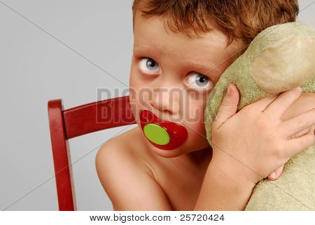 Young boy with big eyes sucking pacifier and hugging favorite toy