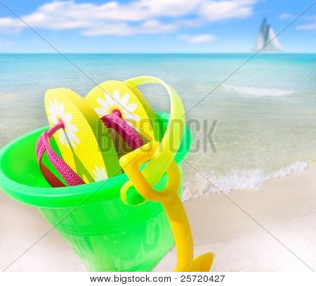 Sand bucket and flipflops on tropical beach