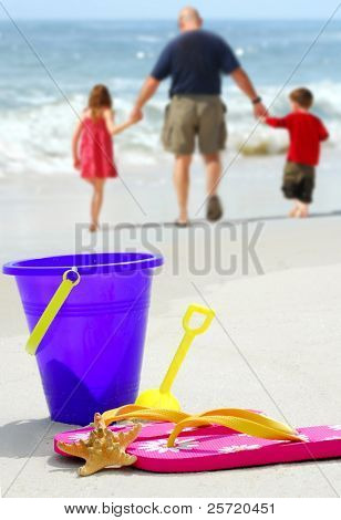Father and children walking by beach pail, flip flops and starfish on pretty beach