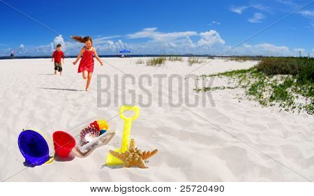 Young girl and boy running towards beach toys in beach sand