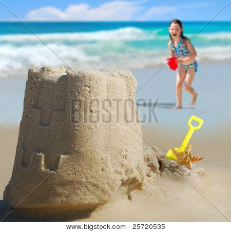 Happy girl running towards Pretty sand castle with ocean in distance