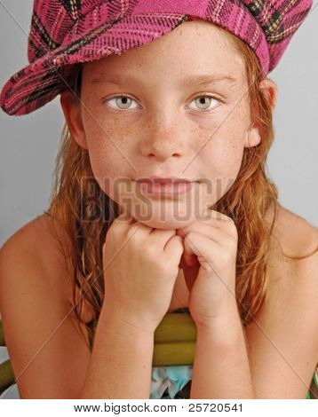 Young girl in plaid hat sitting on chair