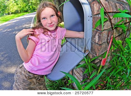 Young girl getting the mail out of streetside, mailbox