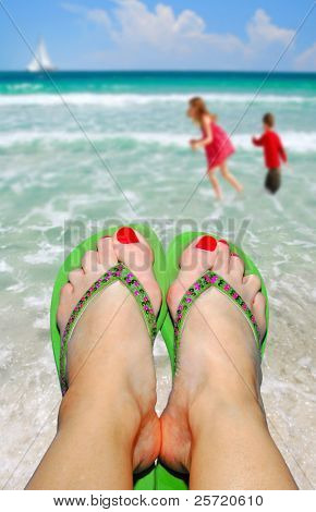 Mom's feet in Flip Flop Sandals watching kids play at Seashore with Sailboat in Distance