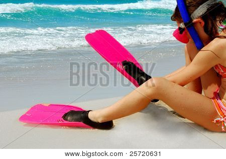 Young girl putting on snorkeling gear on beach