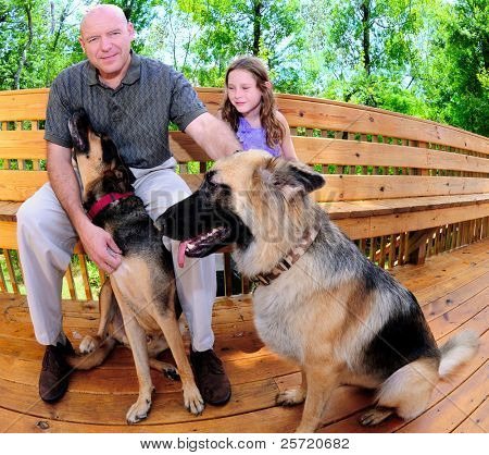 Father and daughter relaxing outdoors with family dogs