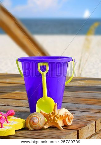 Bucket, shells, and flipflops with sailboat in distance
