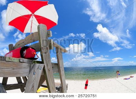 Lifeguard stand and umbrella at beach with girl playing in distance