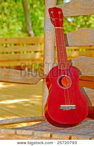 Ukulele string instrument on old rocking chair on porch
