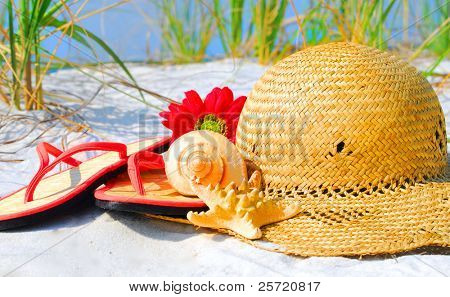 Straw flip flops and hat on beach dune by shells