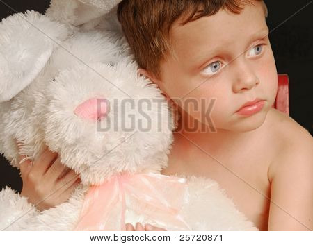 Cute young boy hugging big stuffed bunny