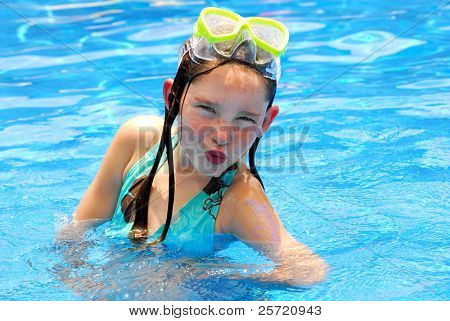 Young girl making silly face while swimming in pool