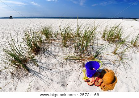 Pretty seashells and straw hat and sandals on beach