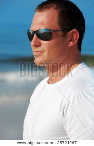 Handsome man wearing sunglasses on beach