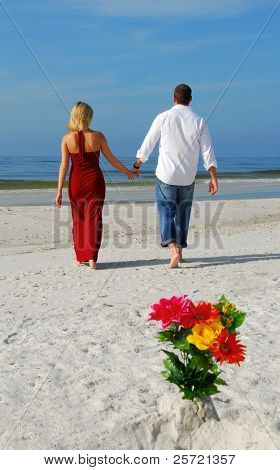 Romantic couple walking away from bouquet in beach sand