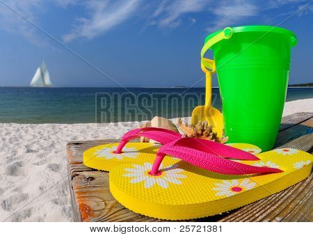 Colorful flip flops, beach pail, and shells on boardwalk by ocean