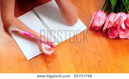 Young girl writing in journal on hardwood floors