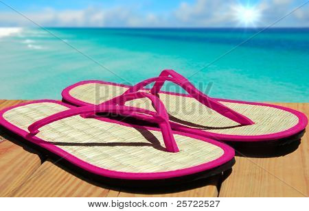 Pretty straw sandals on pier overlooking beautiful ocean
