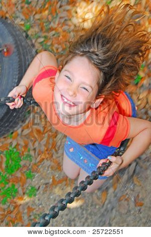 young girl swinging happily on swing at park