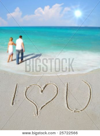 I Love You written in sand by couple with sailboat in distance