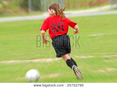 Young soccer player on field chasing moving ball