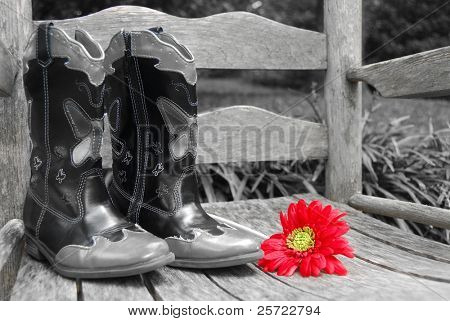 Red gerber daisy on old rocker by cowboy boots